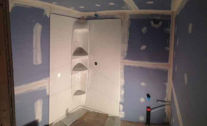 Day 8: A layer of sound insulation followed by two layers of drywall and the first coat of drywall. And, the shower wall system, chosen by the homeowner, is installed.