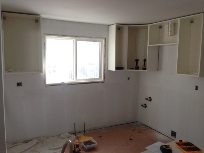 Day 17: Upper kitchen cabinets going in.