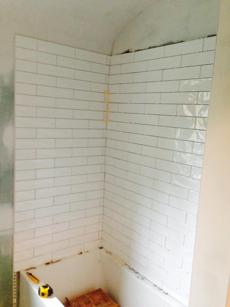 Day 10: Offset subway tiles from Astro Design Centre. The homeowners went back and forth on whether to tile along the curve, but that would mean the tiles on the curved wall would not line up with the tiles on the straight wall, so they went with stopping the tiles before the curve.