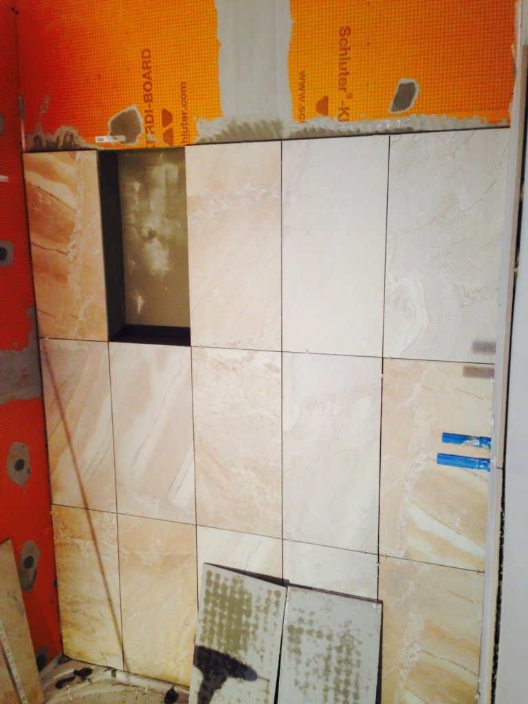 Day 13 of turning two bathrooms into one: shower wall tiles going in along with a recessed storage area.
