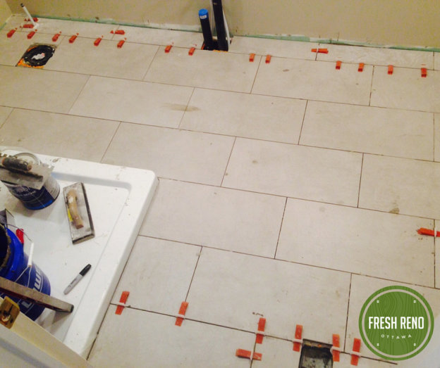 """Bathroom reno day 8: """"Downtown Grey"""" 12 x 24 floor tiles from Ceragres installed. Now onto the shower walls. Nicole of Solace Interiors has made very nice choices for the clients."""