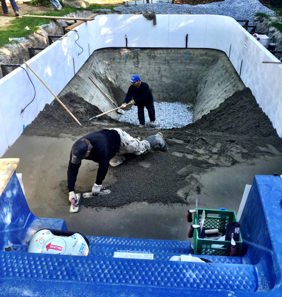 "Mark and Jo, pool specialists, ""grouting"" the bottom of the pool. This makes a smooth base for the pool liner. When a liner costs $6,000, you do want a perfect base that won't cause any rips."